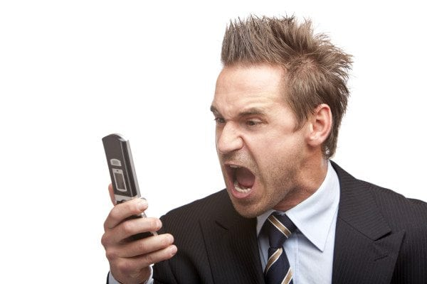 Businessman has stress and sreams into mobile phone
