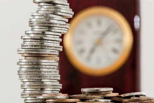 coins stacked high clock in background