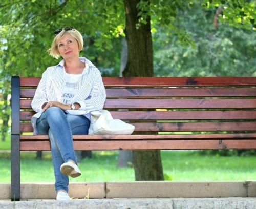 woman on bench with trees