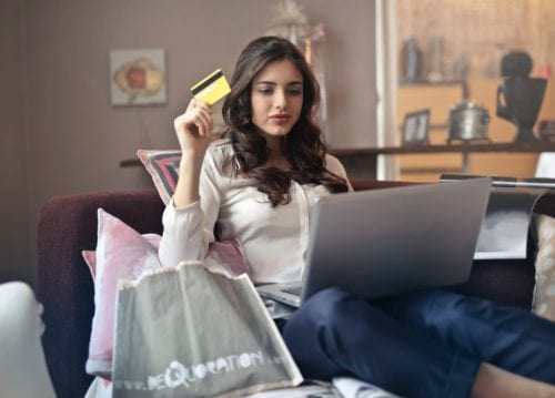 Young woman holds credit card as she shops online