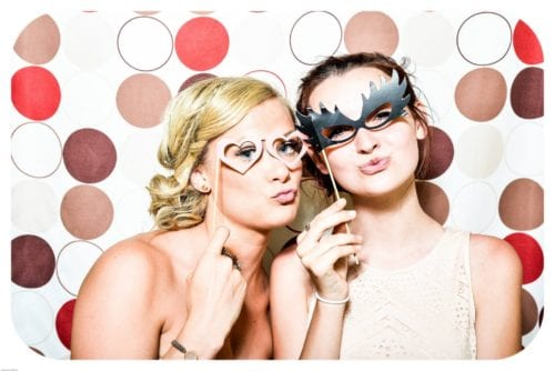 Two women pose for a picture wearing masquerade eye wear