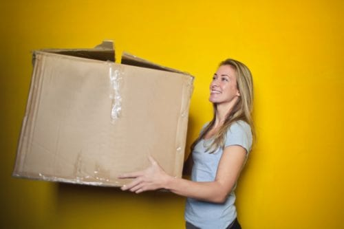 Young woman carrying a big brown box
