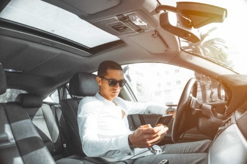 Young man looks at his phone from behind the wheel of a car