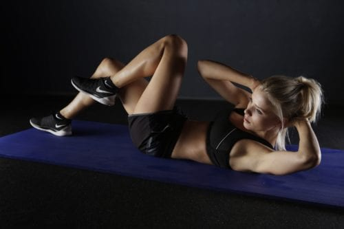 A woman is on a mat doing crunches.