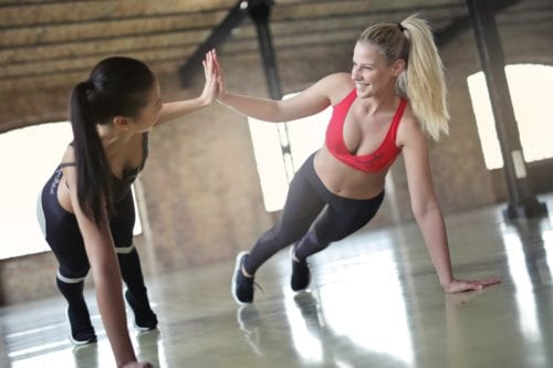 Two women high five during a set of push ups
