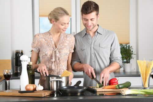 A happy couple cooking together in the kitchen
