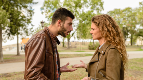 a man and woman arguing at the park