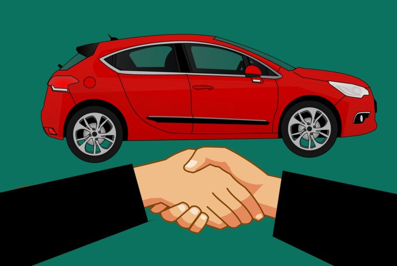 Two people shaking hands in front of a car
