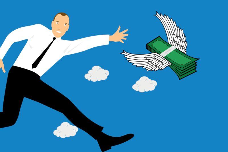 Businessman chasing flying money