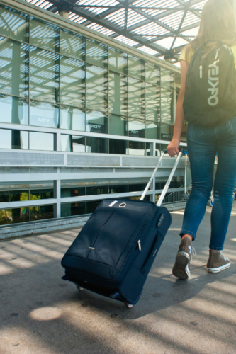 A woman pulling a suitcase towards an airbnb vs hostel